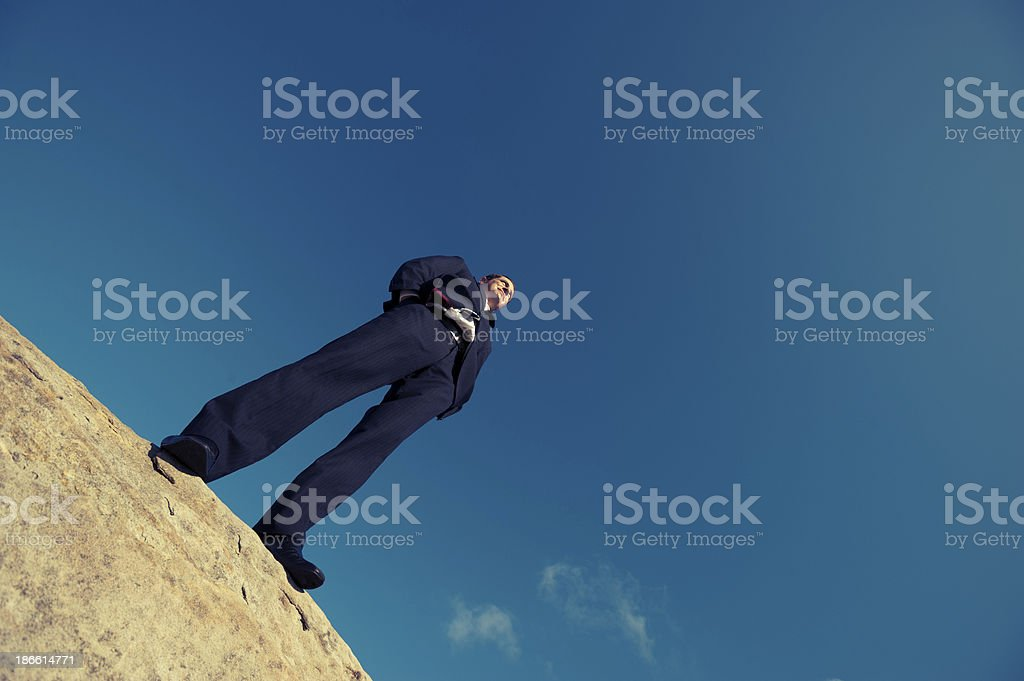 Confident businessman on top of a mountain royalty-free stock photo