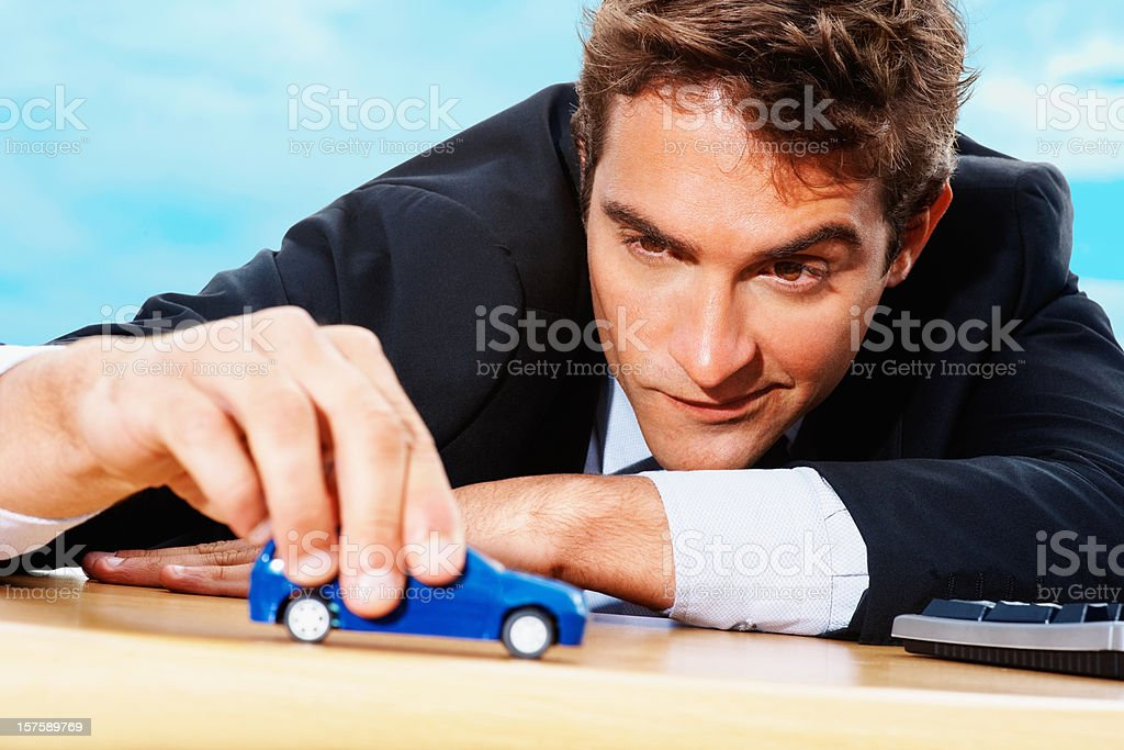 Confident businessman playing with a blue toy car royalty-free stock photo