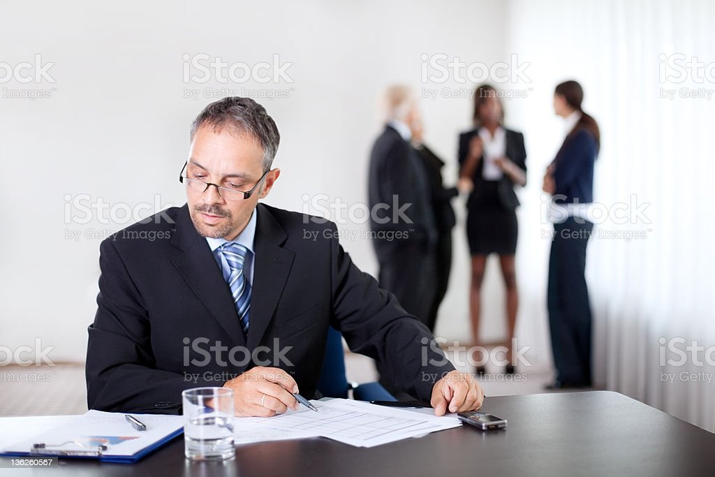 Confident businessman reading and writing royalty-free stock photo