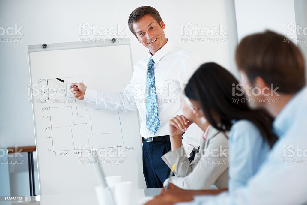Confident businessman reporting sales figures to his team stock photo