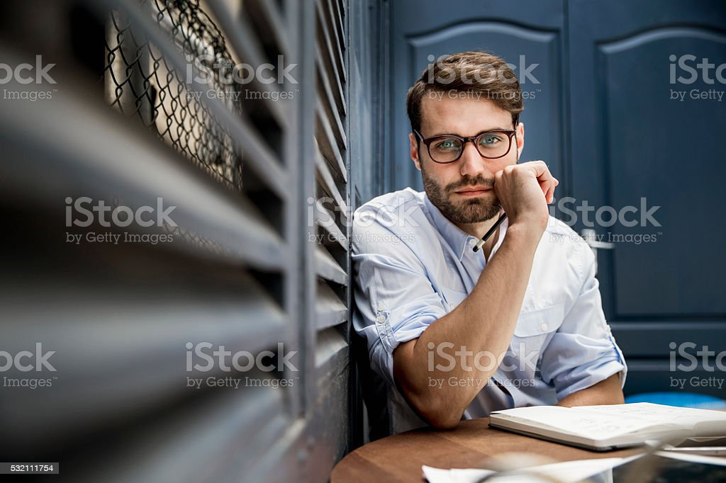 Confident businessman sitting at desk in office stock photo