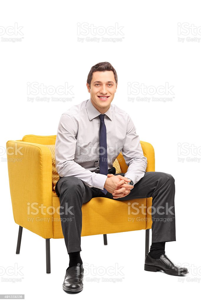 Confident businessman sitting in an armchair stock photo
