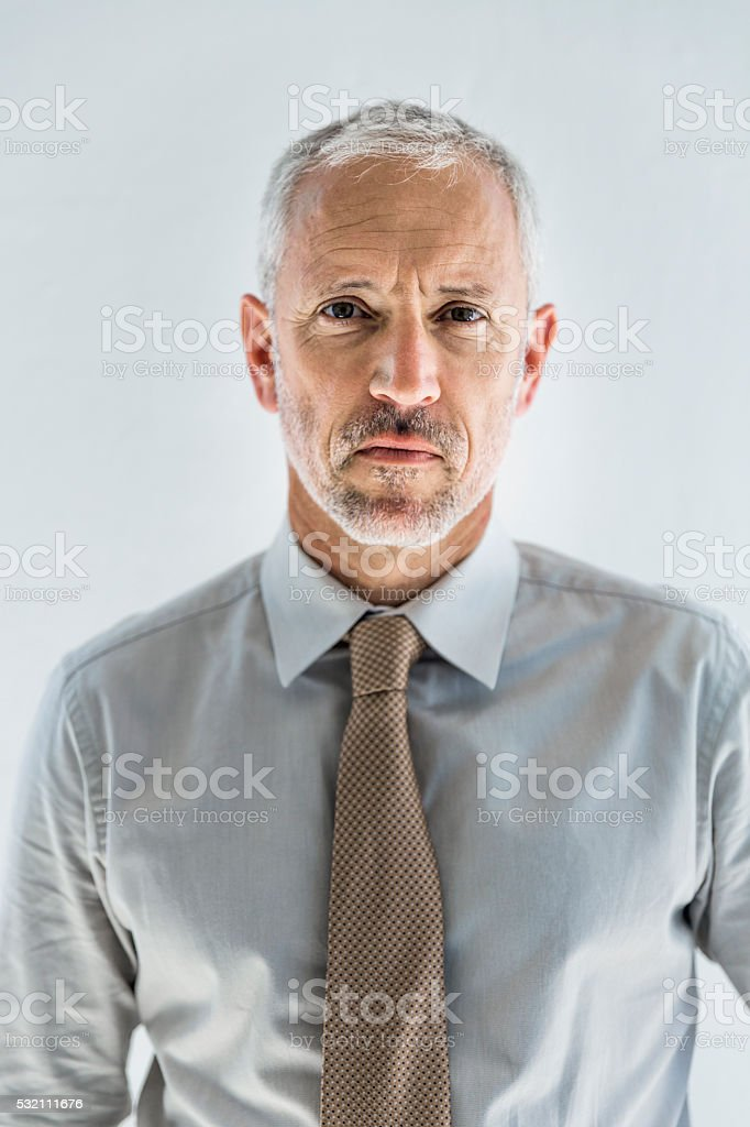 Confident businessman standing against white wall stock photo