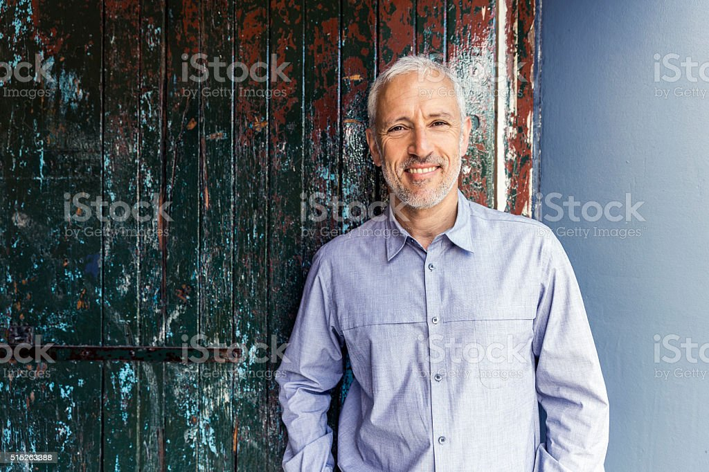 Confident businessman standing against wooden wall stock photo