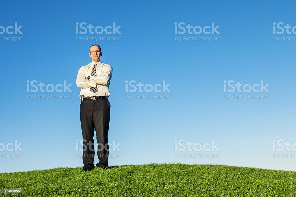 Confident Businessman Standing in Grassy Field royalty-free stock photo