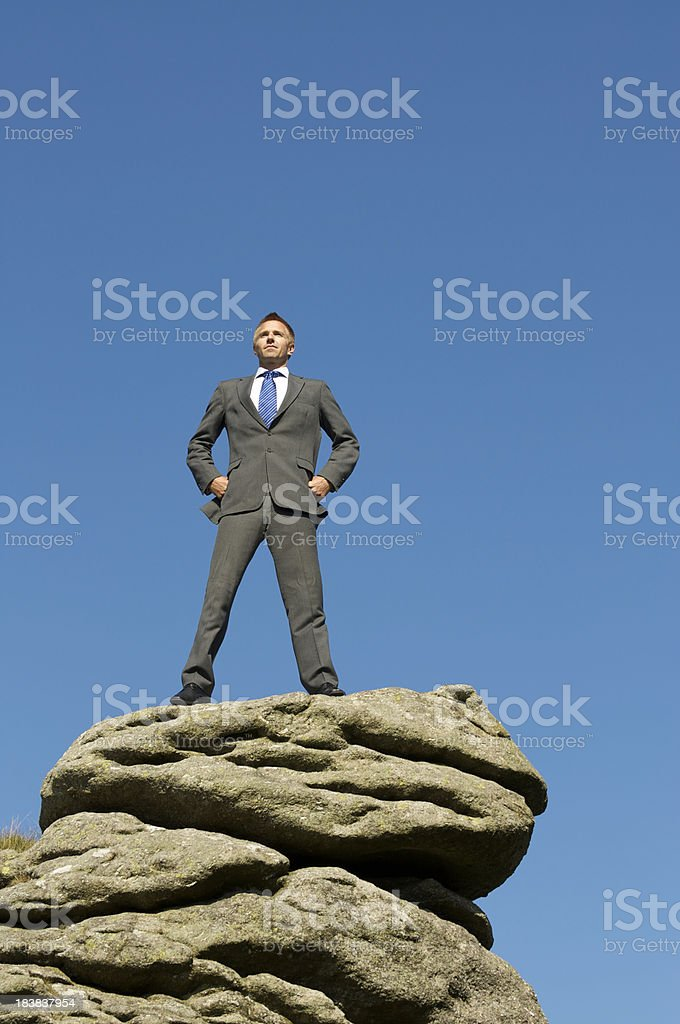 Confident Businessman Standing on Mountaintop w Hands at Hips royalty-free stock photo
