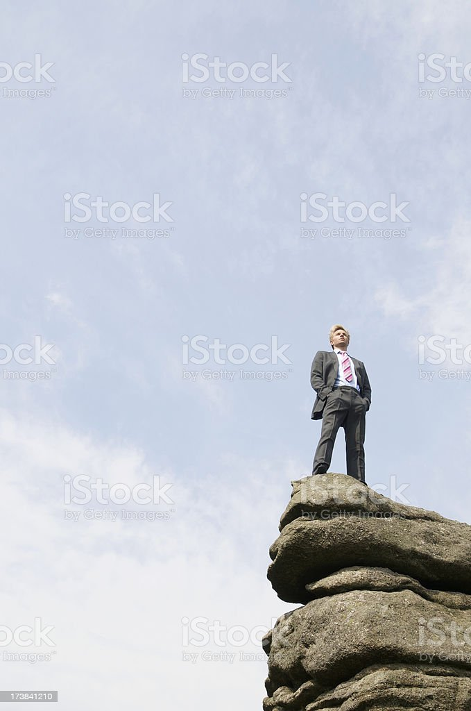 Confident Businessman Standing Tall Outdoors on Top of Rock royalty-free stock photo