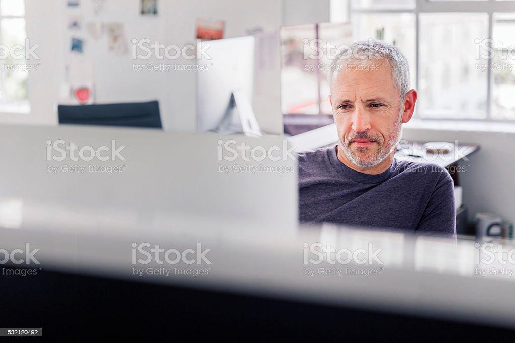 Confident businessman using desktop PC in office stock photo