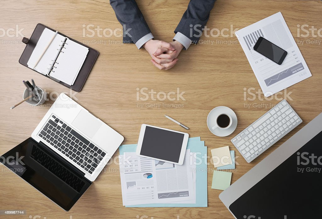 Confident businessman with hands clasped stock photo