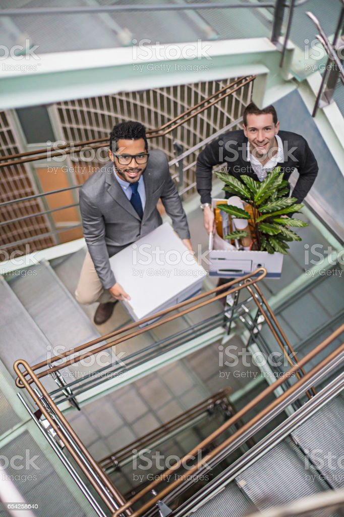 Confident businessmen with belongings on steps stock photo