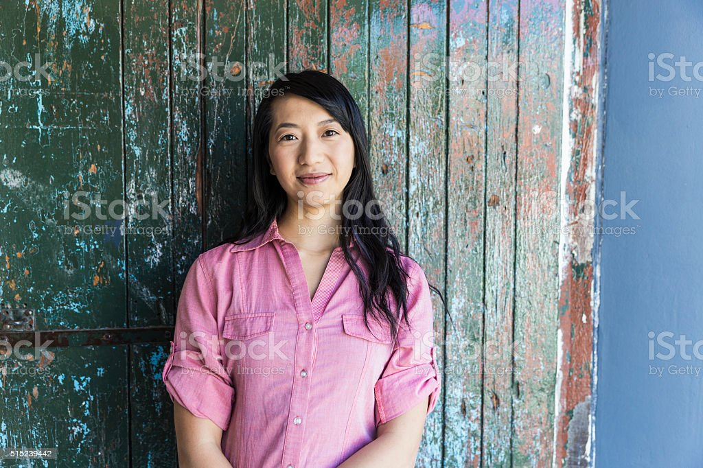 Confident businesswoman against wall in office stock photo