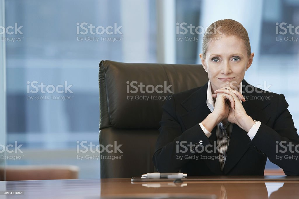Confident Businesswoman At Conference Table stock photo