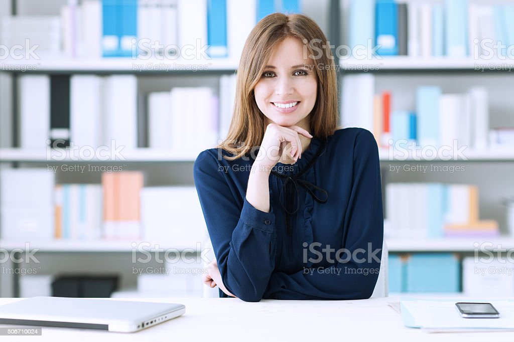 Confident businesswoman at desk stock photo