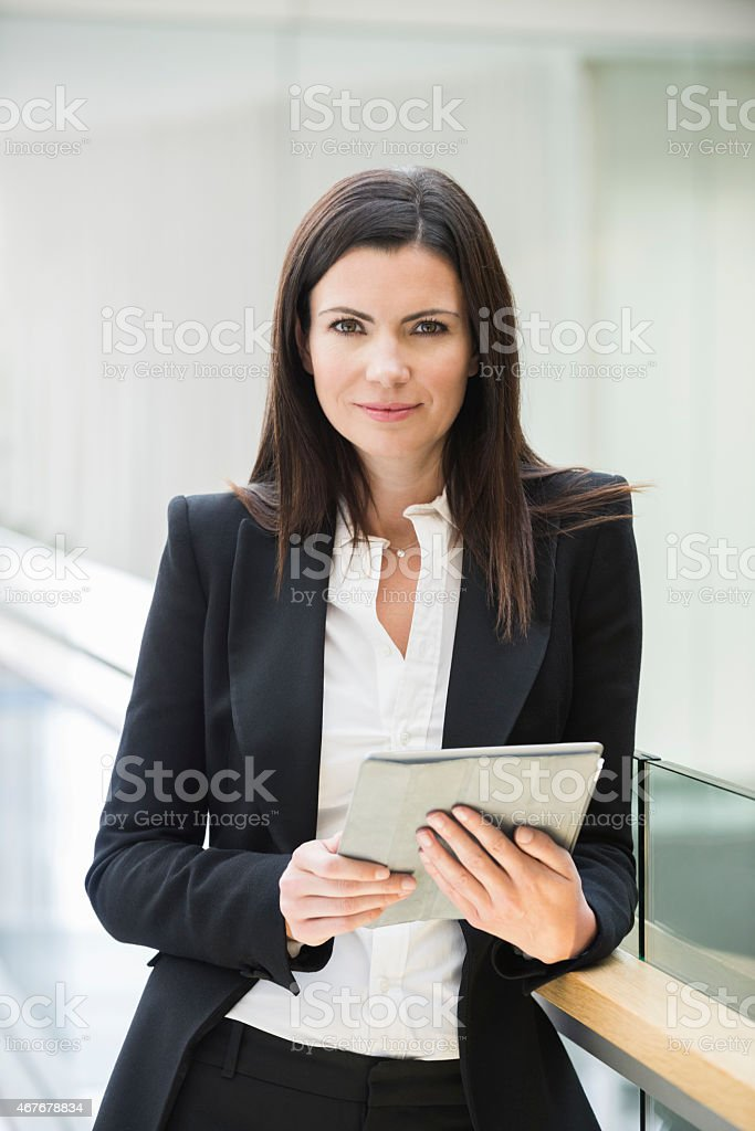 Confident Businesswoman Holding Digital Tablet In Office stock photo