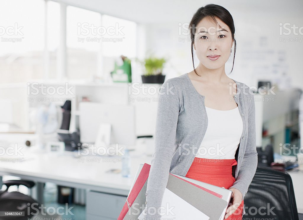 Confident businesswoman holding folders in office stock photo