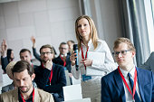Confident businesswoman holding microphone while asking questions during seminar