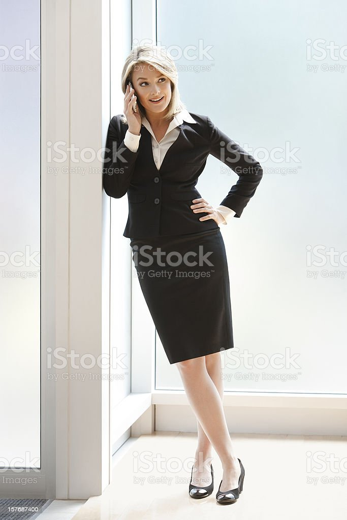 Confident Businesswoman On The Phone Standing In Her Office royalty-free stock photo