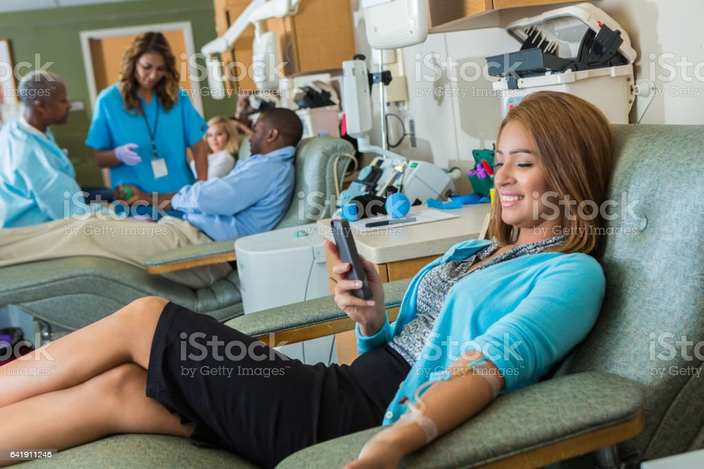 Confident businesswoman passes the time while donating blood stock photo