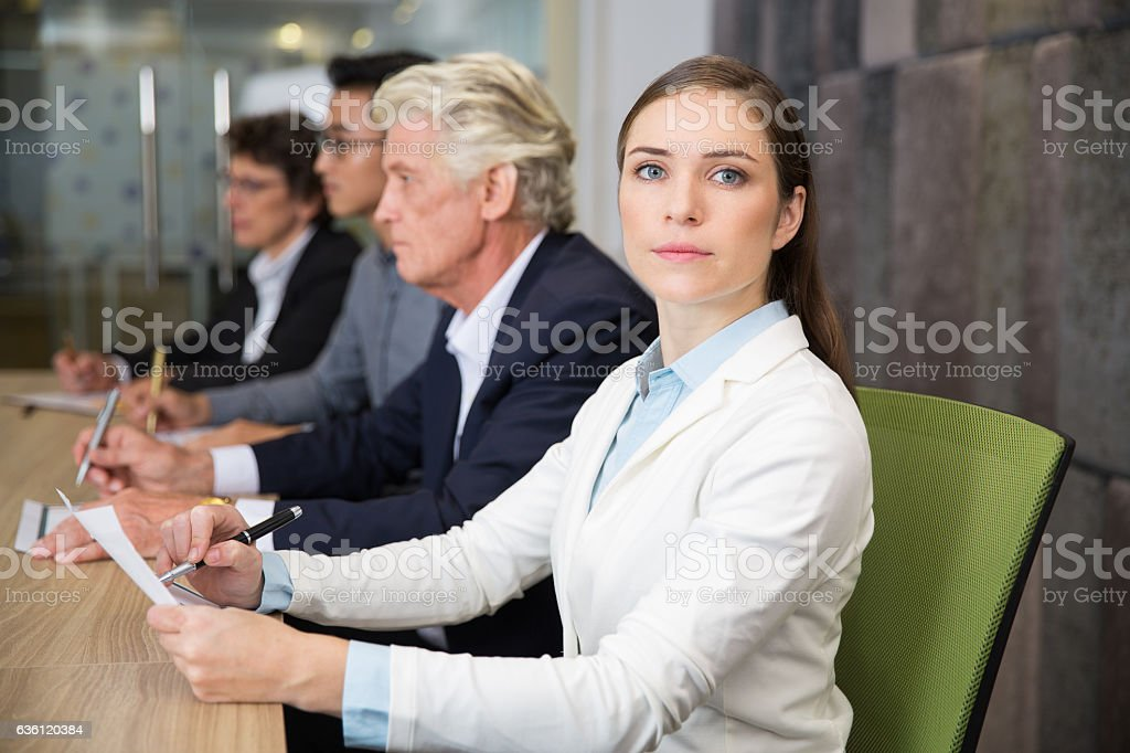 Confident businesswoman sitting at conference stock photo