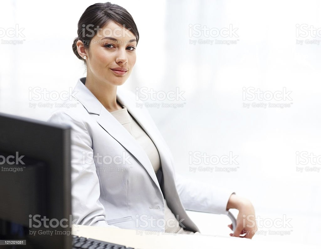 Confident businesswoman sitting in her office and looking at you stock photo