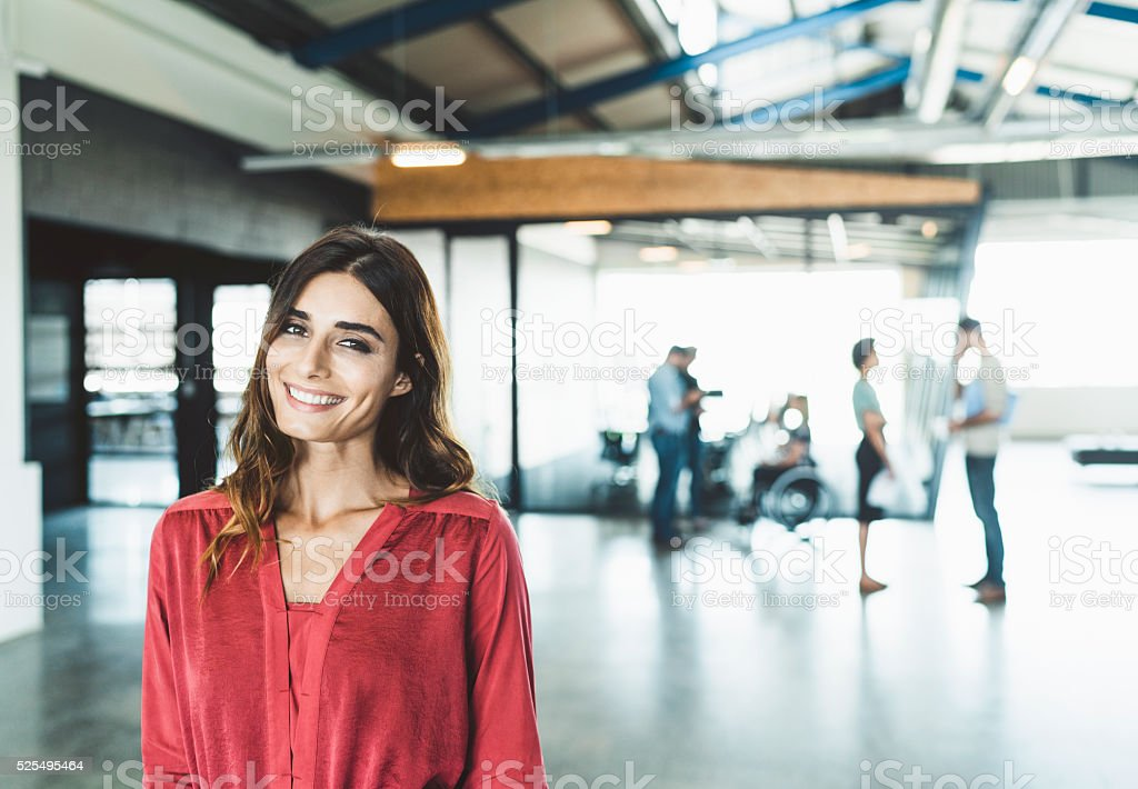 Confident businesswoman smiling in creative office stock photo