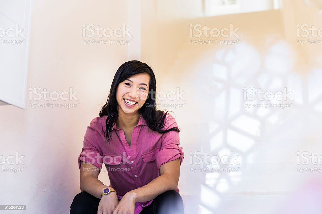 Confident businesswoman smiling while sitting in office stock photo