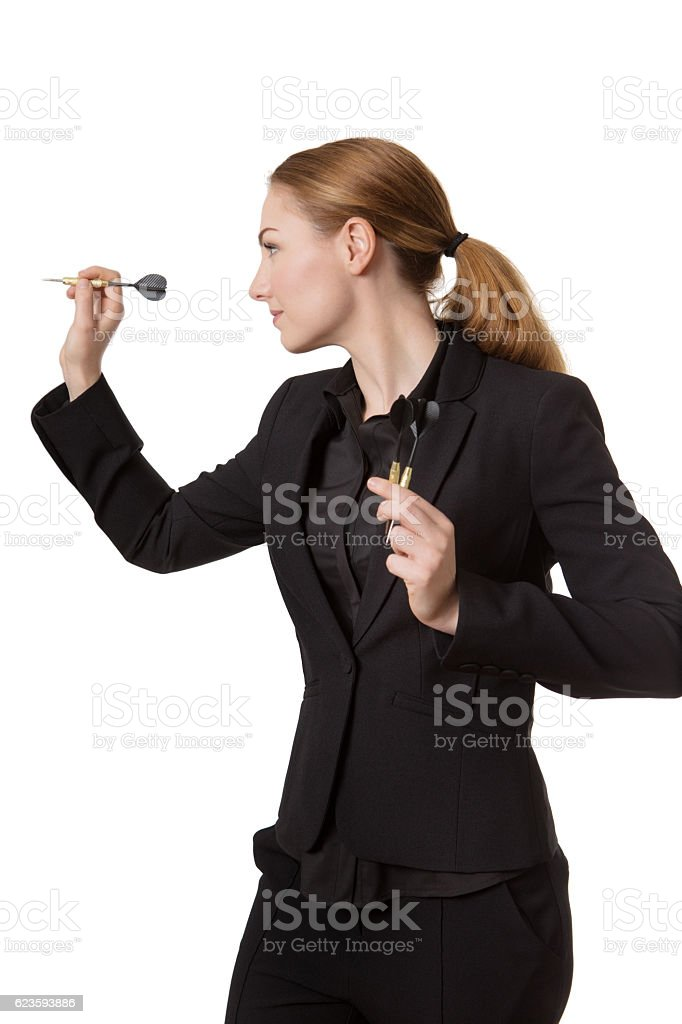 Confident businesswoman throwing dart stock photo