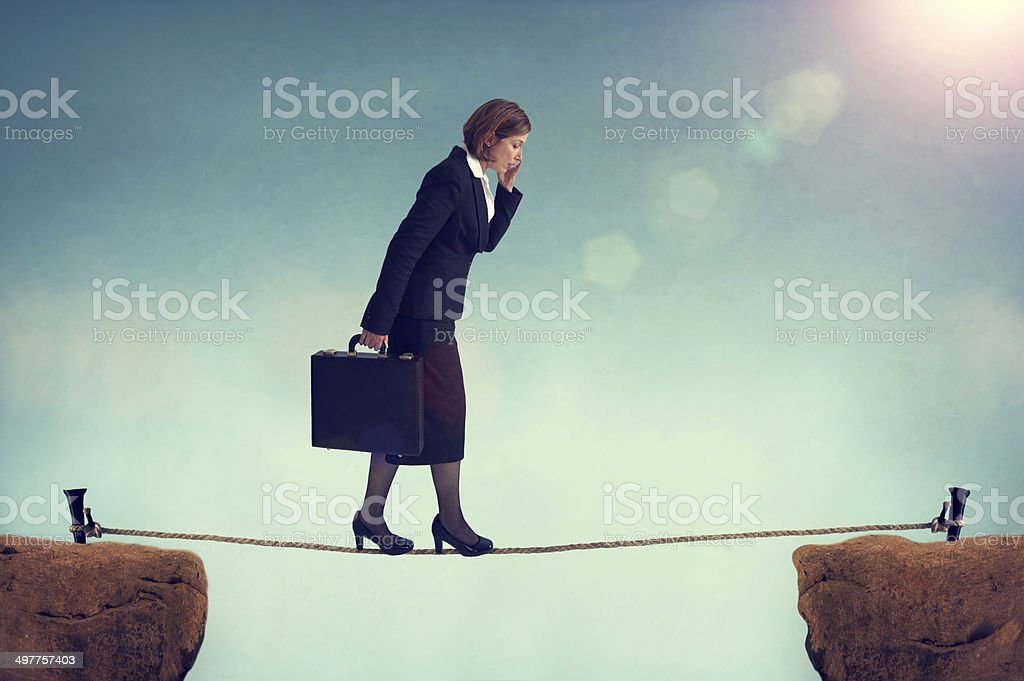 confident businesswoman walking a tightrope stock photo