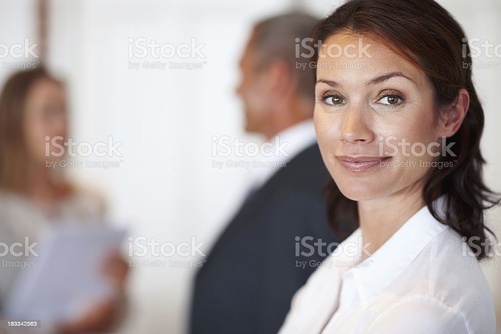 Confident businesswoman with colleagues behind royalty-free stock photo