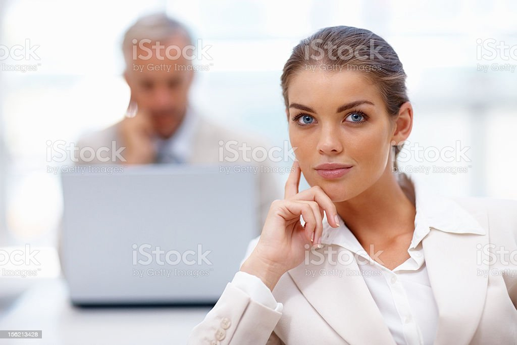 Confident businesswoman with colleagues using laptop in background royalty-free stock photo