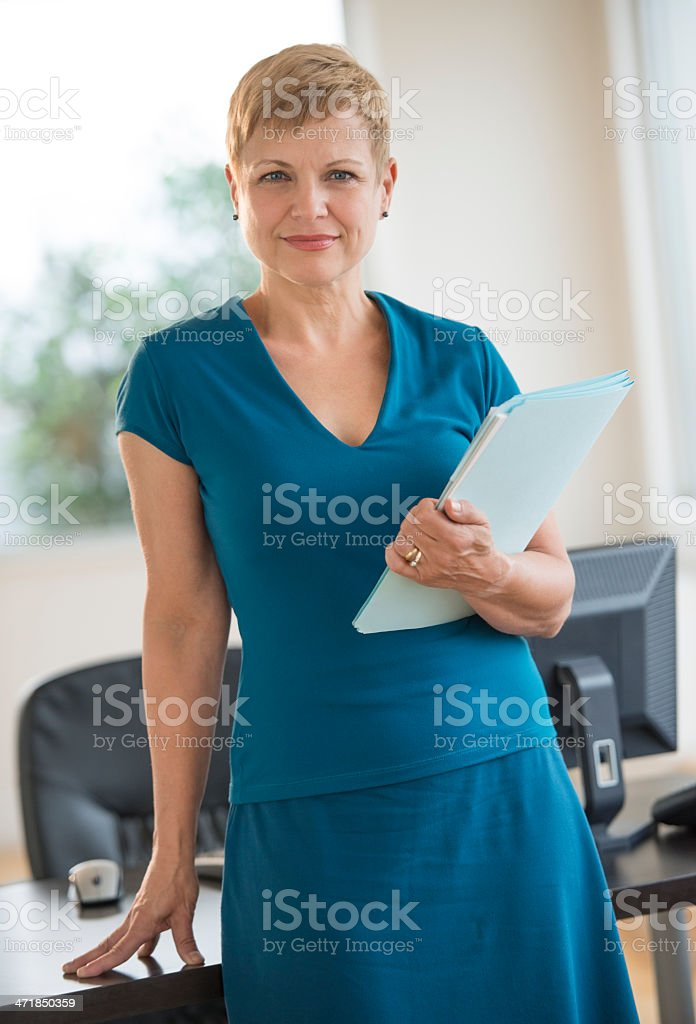Confident Businesswoman With File Standing At Desk royalty-free stock photo