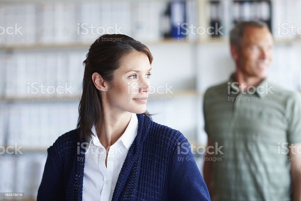 Confident businesswoman with male colleagues in the background royalty-free stock photo