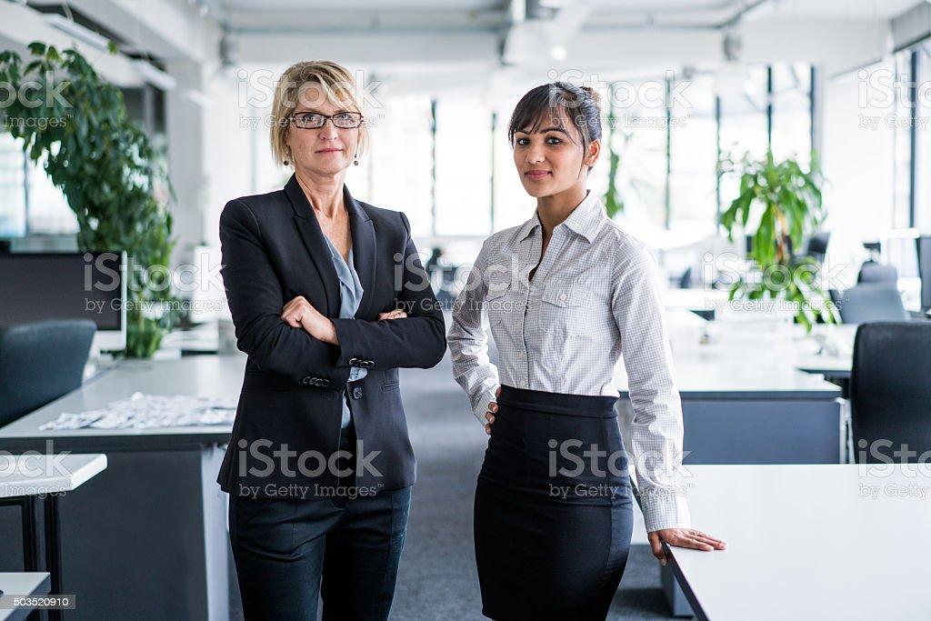 Confident businesswomen standing in office stock photo