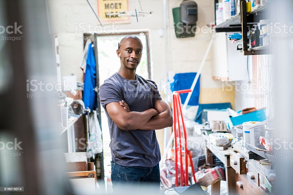 Confident carpenter standing with arms crossed in workshop stock photo