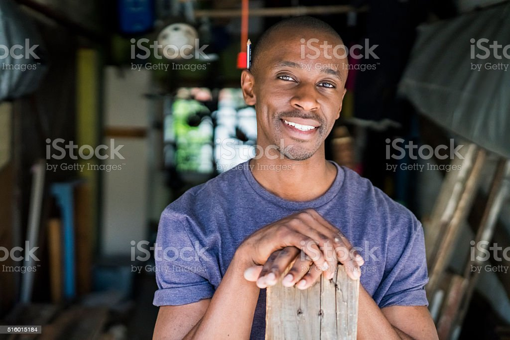 Confident carpenter with plank in workshop stock photo