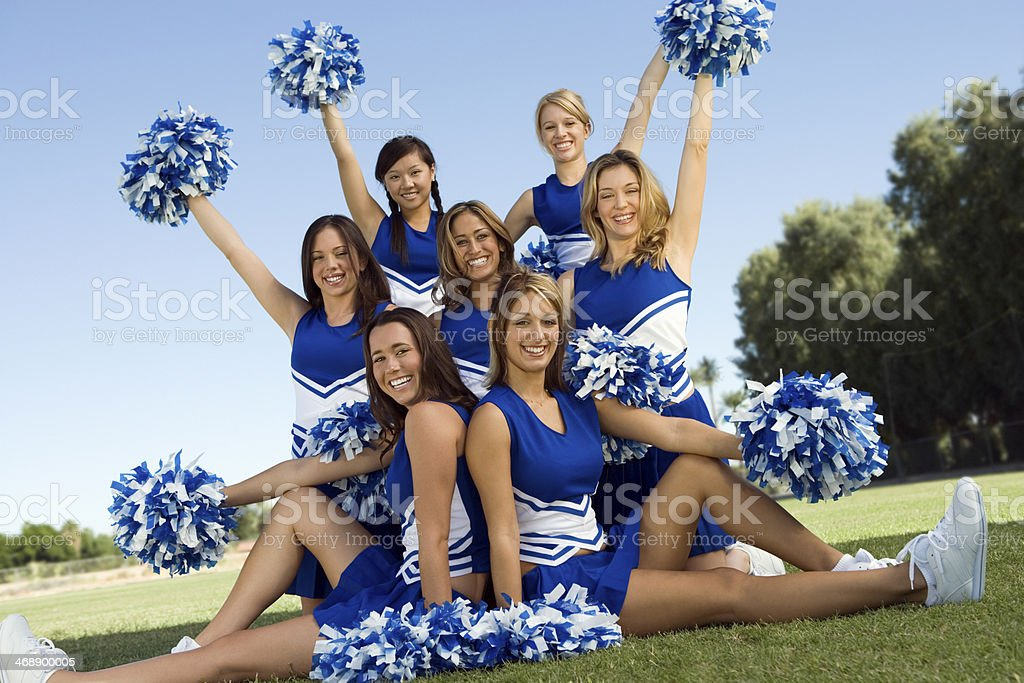 Confident Cheerleaders Holding Pompoms On Field stock photo