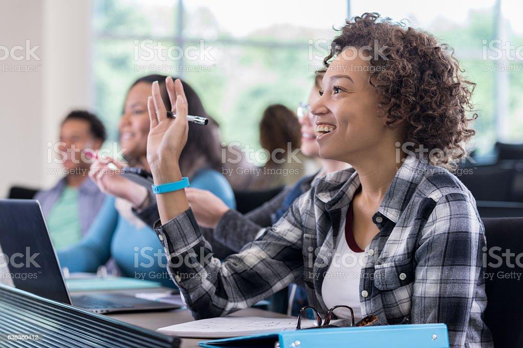 Confident college student raises hand in class stock photo