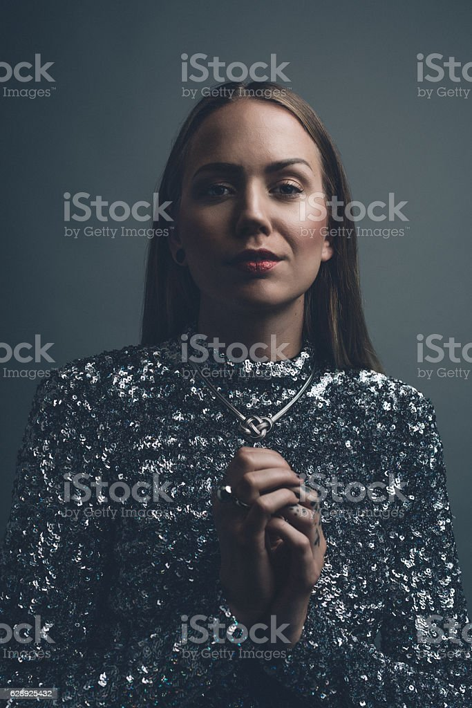 Confident cool real woman studio portrait in party dress stock photo