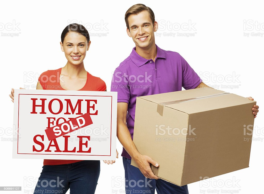 Confident Couple With Real Estate 'Sold' Sign And Cardboard Box royalty-free stock photo