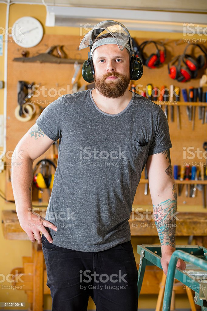 Confident craftsman with safety mask and earmuffs in workshop stock photo