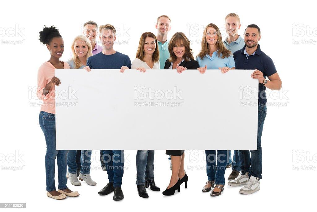 Confident Creative Business Team Holding Blank Billboard stock photo