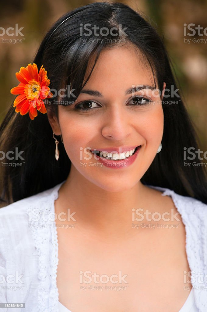 Confident cute young woman with flower on head stock photo