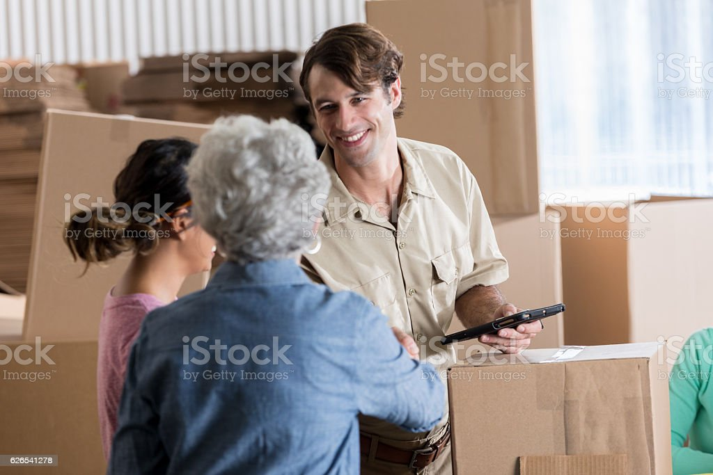 Confident delivery person picks up package from small business owners stock photo