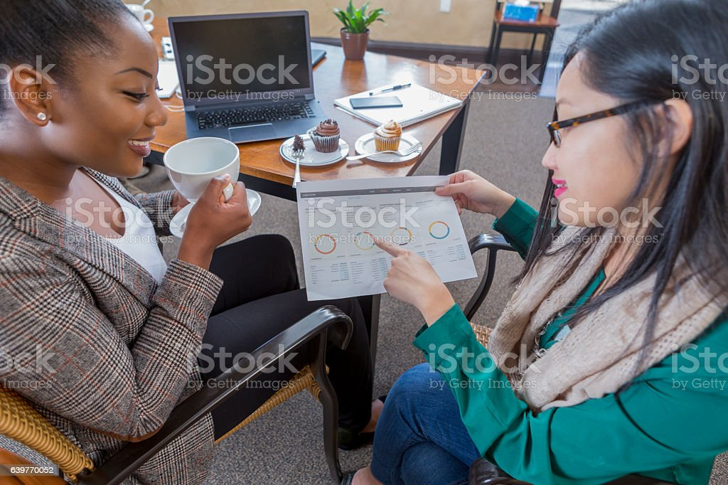 Confident diverse business women review document together stock photo