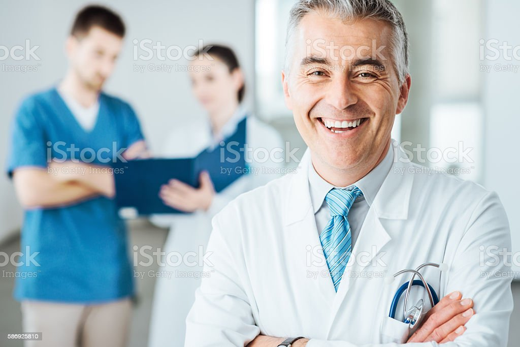 Confident doctor at hospital posing stock photo
