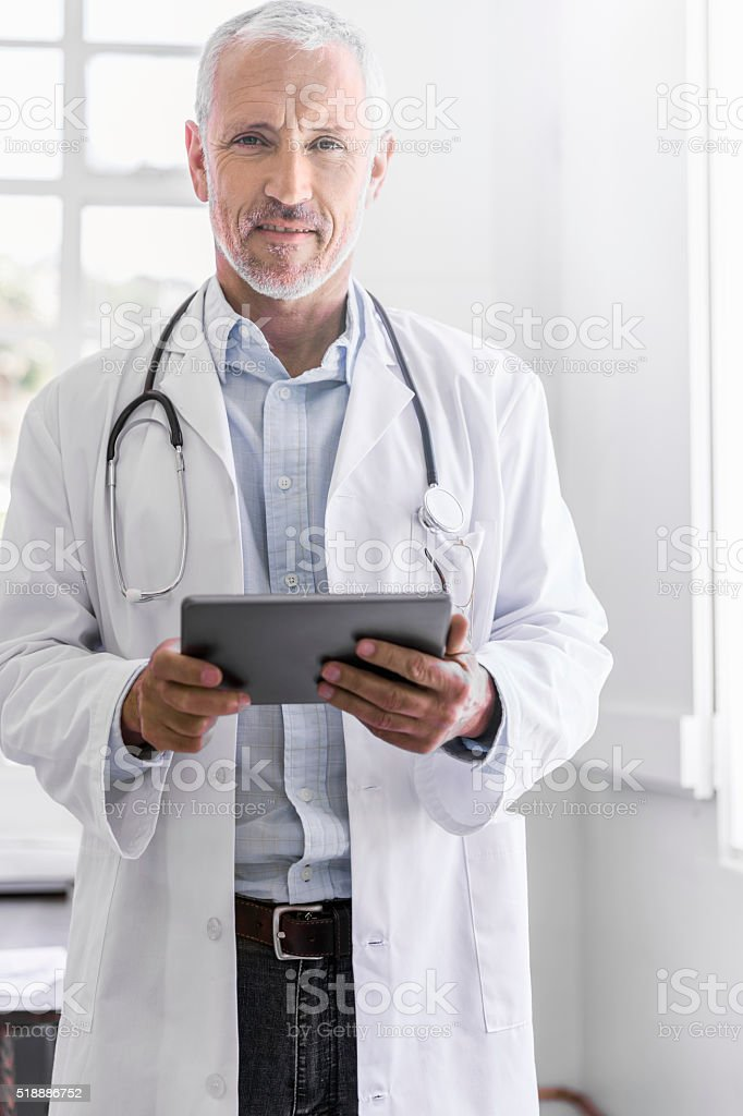 Confident doctor holding digital tablet in clinic stock photo