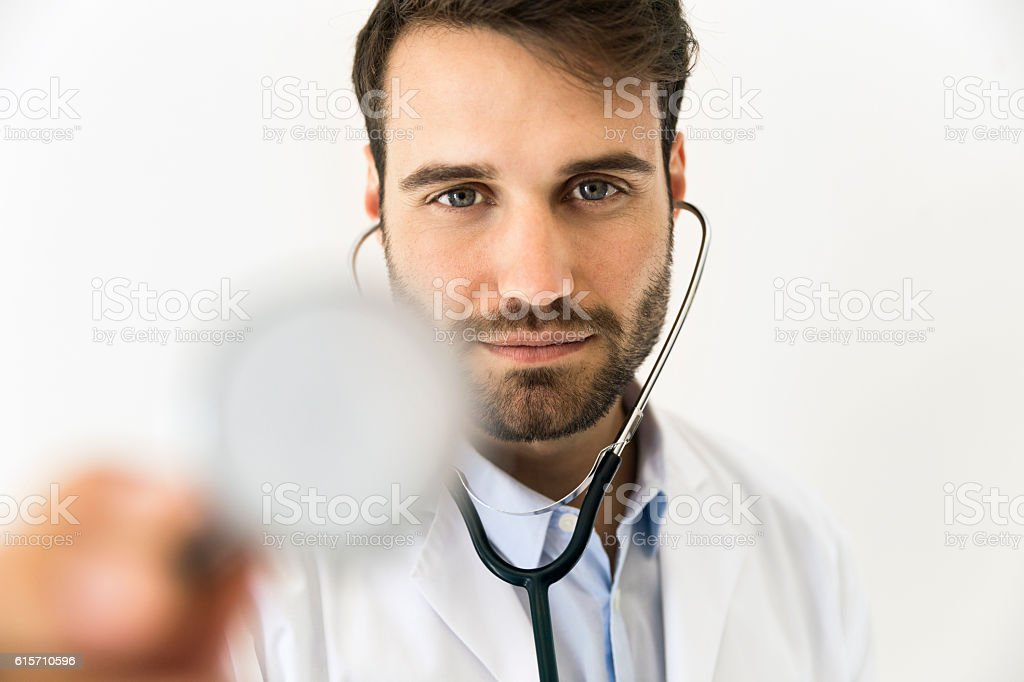 Confident doctor holding stethoscope at clinic stock photo