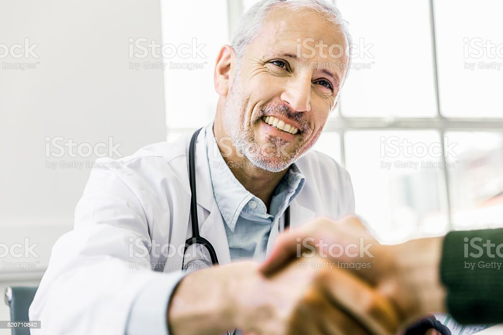 Confident doctor shaking hands with patient stock photo