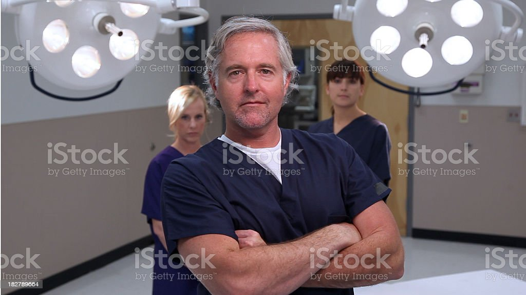 confident doctor surgeon with nurses at hospital stock photo