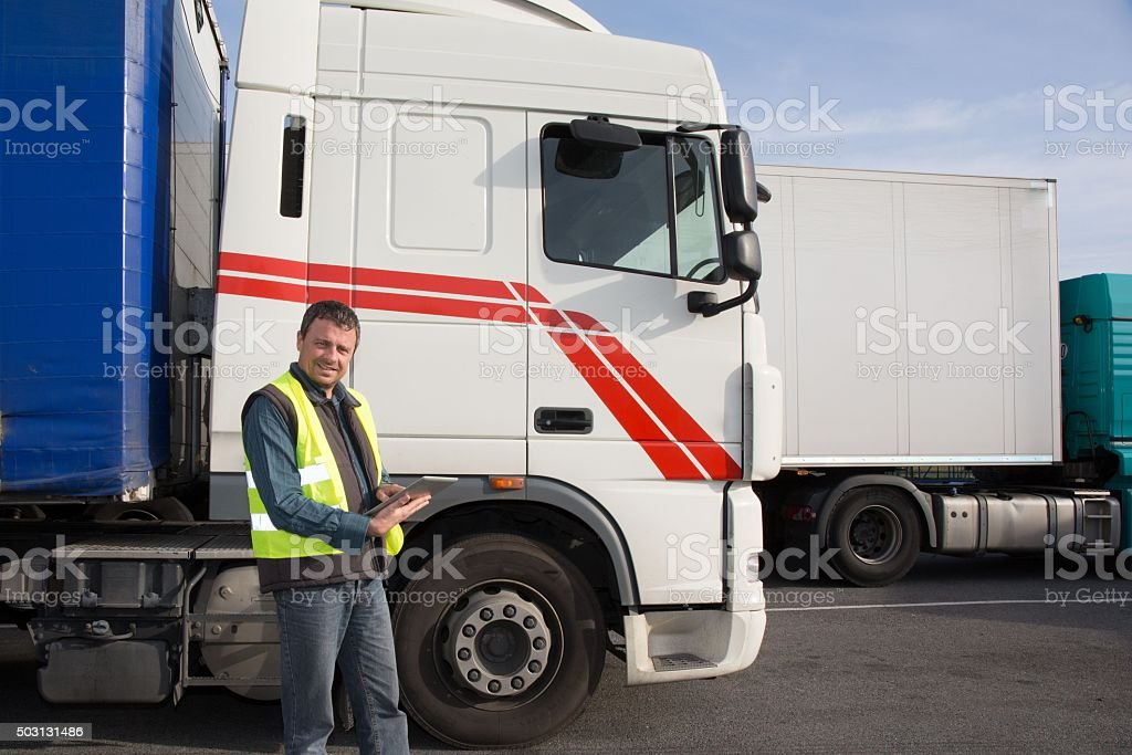 Confident driver or forwarder in drivers cap of truck stock photo